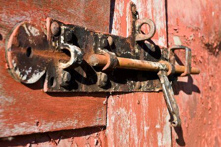 door bolt: Close up de oxidado antiguo cerrojo de puerta en puerta de granero con peeling de pintura.