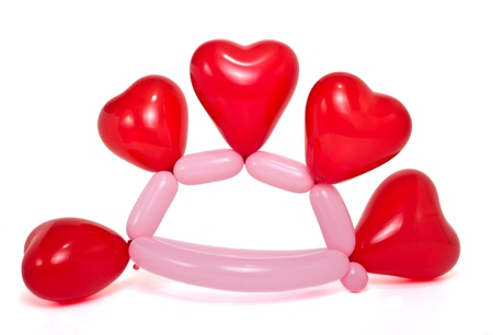 Heart decorated hat made from vibrant twisted balloons isolated on white background. photo