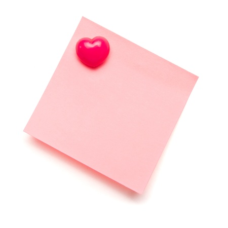 Light pink self adhesive post it note with heart shape push pin on white.