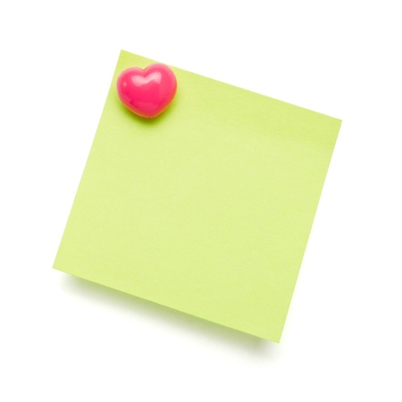 Green self adhesive post it note with heart shape push pin on white.