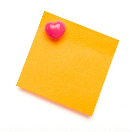 Orange self adhesive post it note with heart shape push pin on white. photo