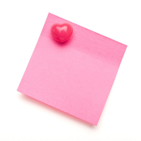 Dark pink self adhesive post it note with heart shape push pin on white. photo