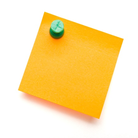 Orange self adhesive post it note with green push pin on white.