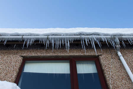Cold snap home maintenance concept of frozen gutters. photo