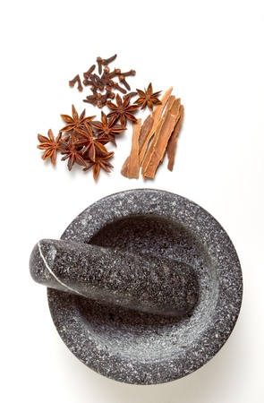 clove of clove: Granite mortar and pestle with winter spices of Cinnamon, cloves and Star Anise Stock Photo