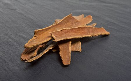 dark grey slate: Pile of Cinnamon bark from low perspective isolated on dark grey slate.