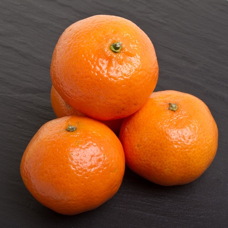 dark grey slate: Clementines from low perspective isolated on dark grey slate background.