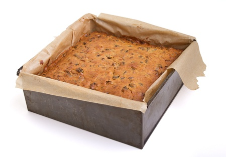 Square christmas fruit cake in baking tin just removed from oven. photo
