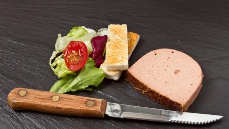 melba: Aperitivos de paté con melba toast soldados y ensalada pequeña sobre fondo oscuro de pizarra. Foto de archivo