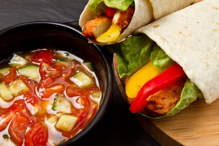 Spicy chicken wrap and pot of vibrant salsa. photo