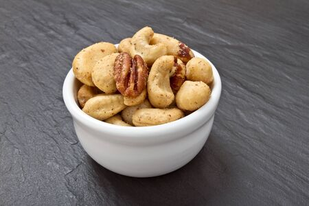 dark grey slate: Mixed Salted Nuts in bowl on dark grey slate background.