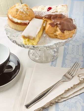 choux bun: Afternoon Tea with selection of cream cakes on glass cake stand,