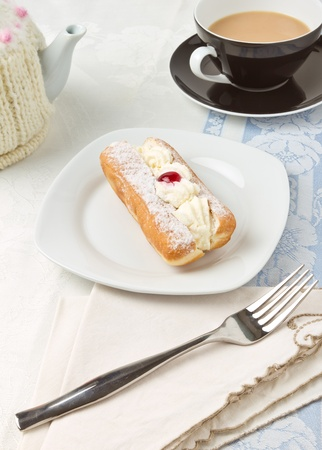Afternoon Tea with cream doughnut decorated with glace cherry. Stock Photo - 8797260