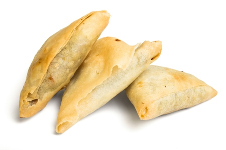 low perspective: Cooked golden Samosas from low perspective isolated on white.