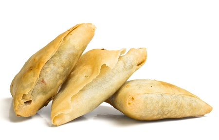 Cooked golden Samosas from low perspective isolated on white.
