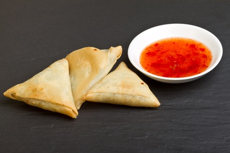 Sweet chilli dipping sauce and golden fried samosas on dark slate background.