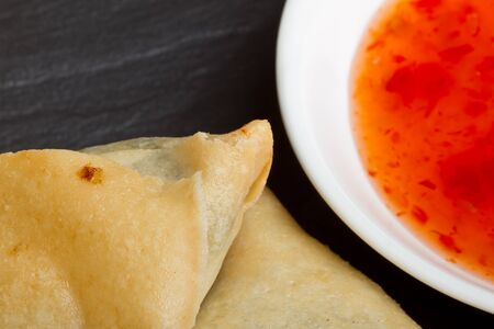 Sweet chilli dipping sauce and golden fried samosas on dark slate background. photo
