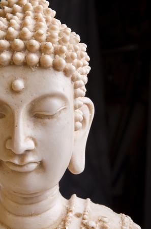 cabeza de buda: Cerca de la cara de estatua de Buddah contra el fondo oscuro.