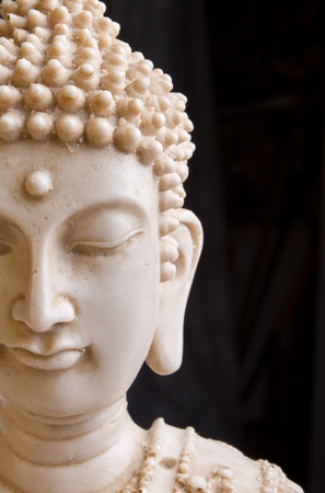 buddah: Close up of Buddah statue face against dark background.