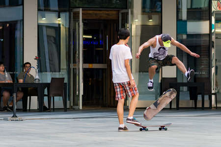 Beijing / China - August 21, 2016: Skaters doing tricks with skateboards in modern Sanlitun area of Chaoyang district in central Beijing, China