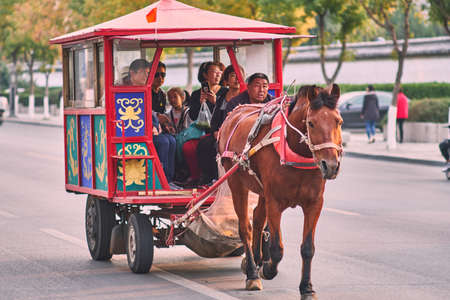 Qufu / China - October 13, 2018: Horse pulling cart with tourists in Qufu, Shandong province, China. Qufu is famous as the birthplace of ancient Chinese philosopher Confucius.