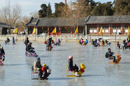 Beijing / China - January 25, 2014: People skating and sliding on sledges on frozen Houhai lake in Xicheng District in central Beijing, China Editorial