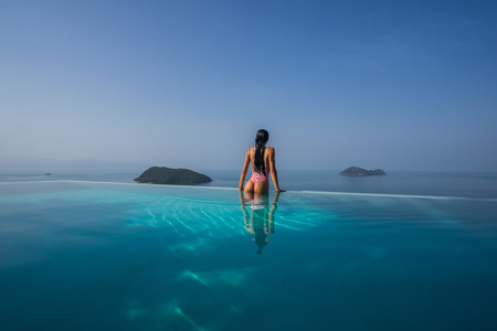 Beautiful girl on the edge of the infinite pool 스톡 콘텐츠