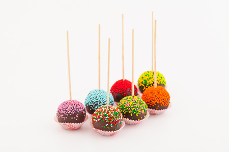 colored cup cake on stick, on white background