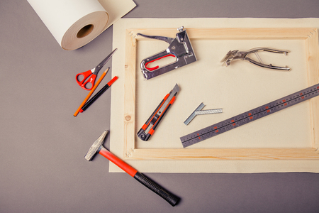 Canvas artist on roll, stretcher for canvas, staple gun and other tools on a gray background