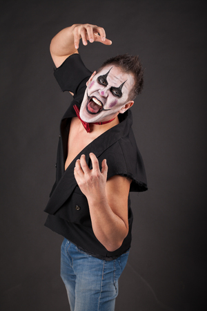 A man in the makeup of an evil clown shows his tongue. The image for halloween. Studio photo on a black background