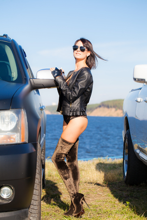 Sexy girl in a lingerie jacket and boots stands on two cars against the background of water and sky