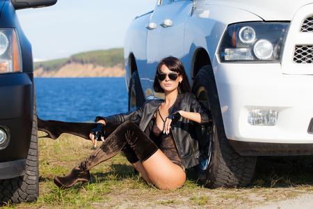 Sexy Mädchen in einer Dessousjacke und Stiefeln, die zwischen zwei Autos auf einem Hintergrund von Wasser und Himmel sitzen