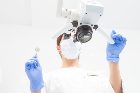 A female dentist is looking into a dental microscope. Bottom view. Focus on the doctor