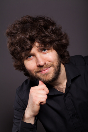 Portrait of a curly-haired man with a bristle. Studio shot on a black background Stock Photo