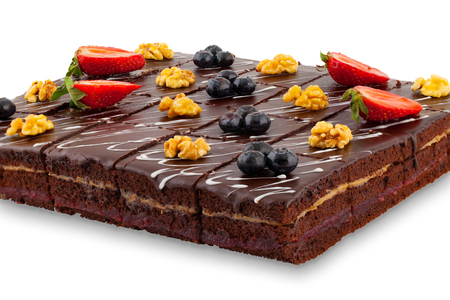 A large chocolate cake with berries and nuts isolated on white background Stock Photo
