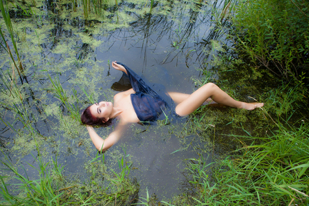 a young woman lies in a swamp covered with a black cloth