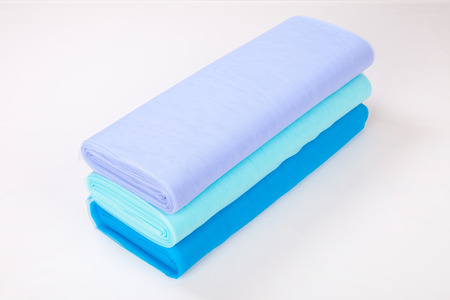 different rolls of fabric lie on a white background. gradient blue