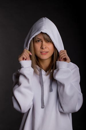 Beautiful young woman in a large white hooded sweatshirt. Studio portrait on black background