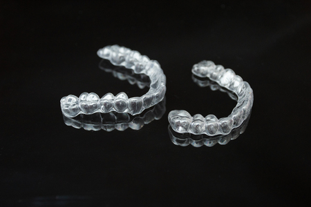 A pair of upper and lower transparent latches or aligners lie side by side on a dark reflective surface against a black background.