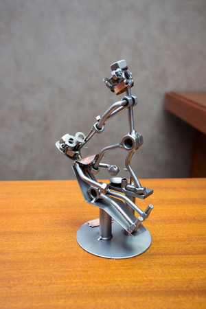 metal figurine of the dentist and the patient on the chair, standing on the table. Imitation of tooth extraction. Souvenir, toy