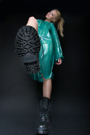 A young beautiful woman in a green rain coat lifted her leg, revealing the sole of a tourist boot. Photo taken photo studio on a black background