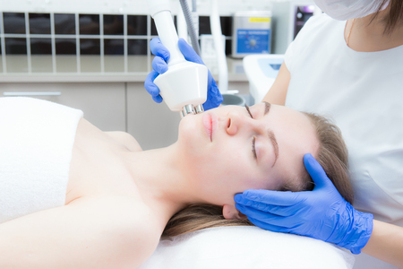 A young beautiful woman receives an electric facial massage on beauty equipment. Cosmetician in gloves. Modern cosmetology