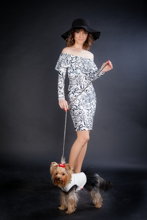 young beautiful woman in black hat with yorkshire terrier on leash in photo studio stands on black background 免版税图像