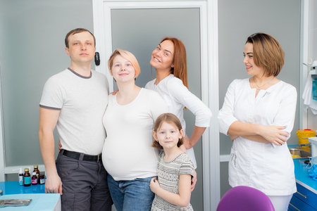 Happy family - dad, daughter, pregnant mother with two young beautiful doctors in a medical clinic. Everyone is looking at the frame