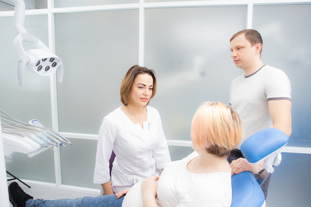pregnant woman and her husband communicate with a dentist in a medical office. Dental treatment for pregnant women