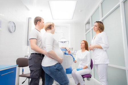 pregnant woman and her husband communicate with two young women dentists in a medical office. Dental treatment for pregnant women