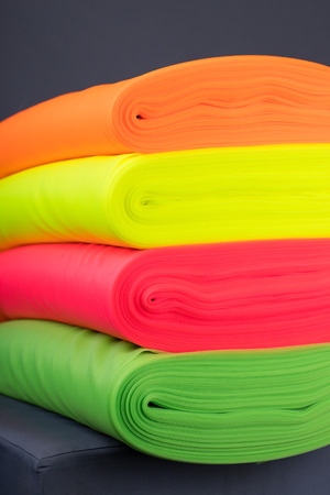 Four rolls of fabric neon colors. Tulle. neatly folded in a row. On a dark background