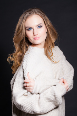 portrait of a young, beautiful woman on a black background, in a big light sweater