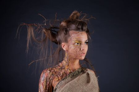 Young beautiful woman in the image of a tree. Hairdo with branches. Shooting in a photo studio on a black background