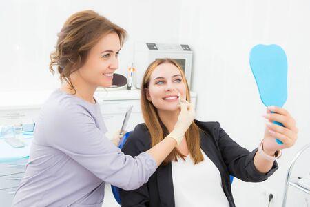 Junge Patientin, wählt die Farbe des Zahns, der Krone, des Furniers und schaut in den Spiegel in der Zahnklinik. Das Konzept von Medizin, Zahnmedizin und Gesundheit